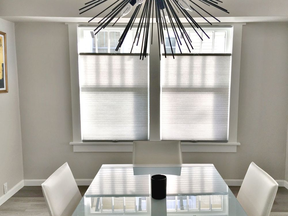 A simple dining room boasting a stunning ceiling light just above the dining table set. The room features hardwood floors and light gray walls.