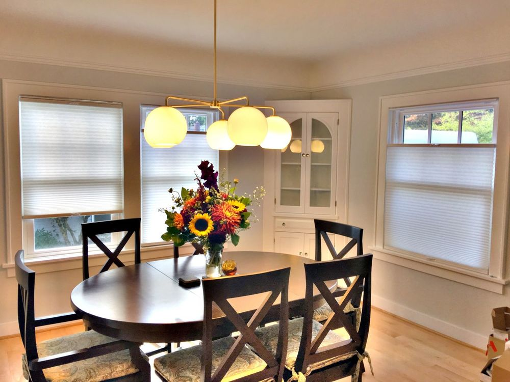 Dining room featuring a classy oval-shaped dining table set lighted by a charming ceiling light and is surrounded by windows featuring window shades.