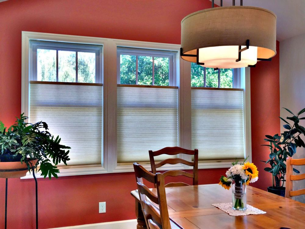 Dining room with wooden dining table and chairs set lighted by a modish ceiling light. The area features a red wall and windows with window shades.