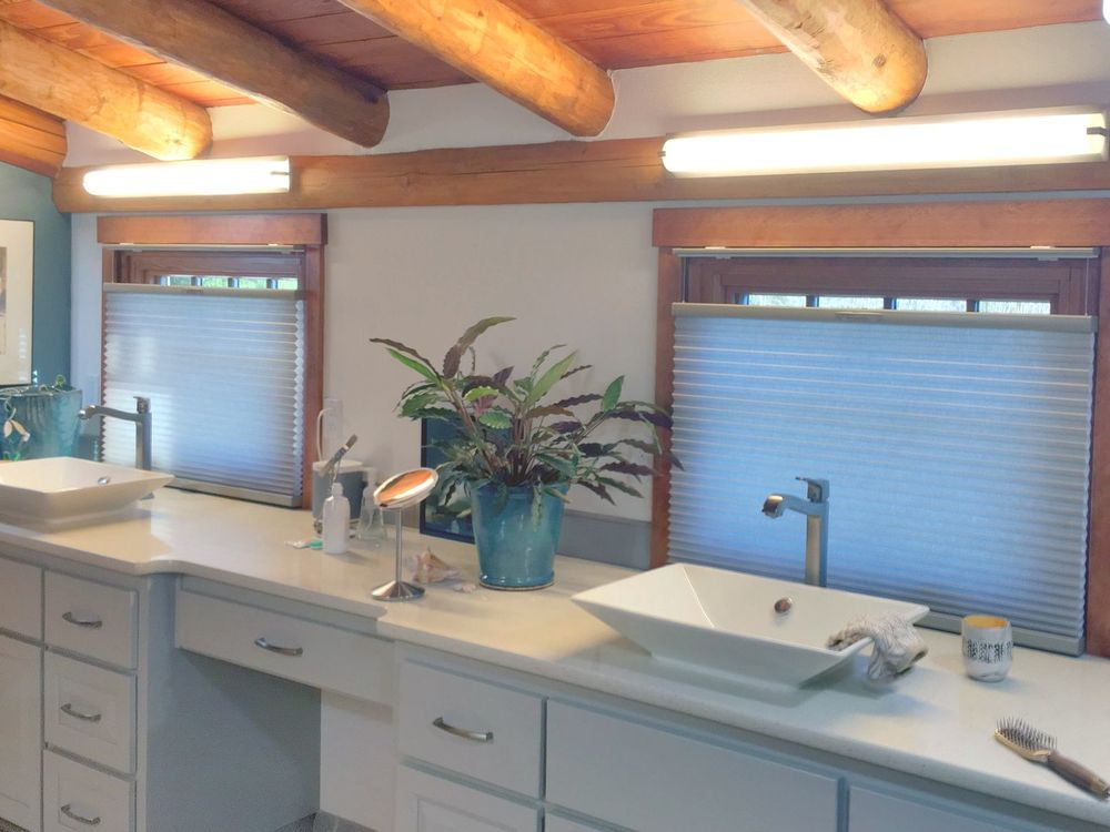 This bathroom features a rustic ceiling with logs beams. It also has a sink counter with two vessel sinks and a powder desk in the middle.