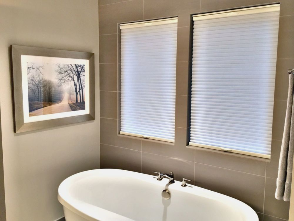 A master bathroom with tiles walls and a freestanding tub, along with windows featuring window shades.