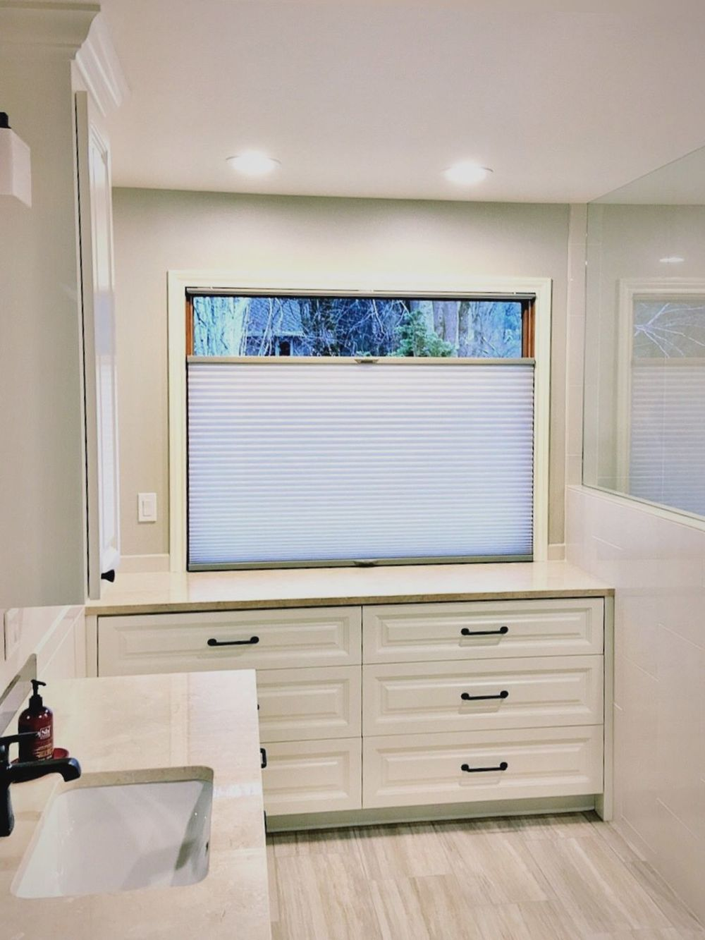 Primary bathroom featuring a single sink counter and cabinetry with a counter, along with a glass window featuring a window shade.