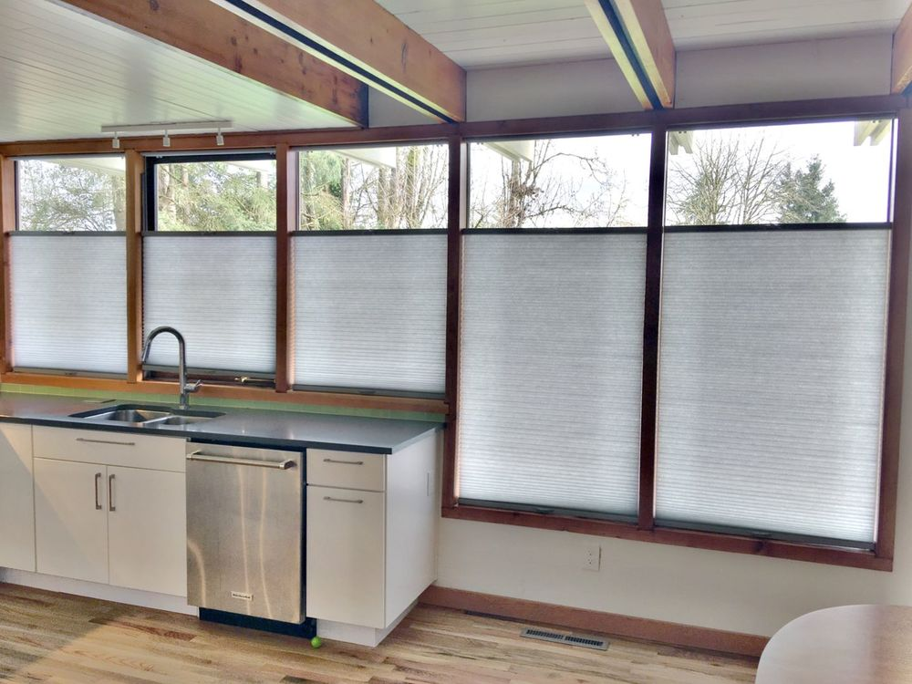 This kitchen features hardwood floors and a ceiling with beams. It also features windows with window shades.