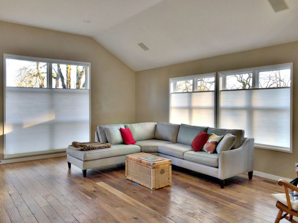 A living space featuring hardwood flooring and brown walls, along with glass windows with window shades. The room also offers a modern L-shaped sofa.