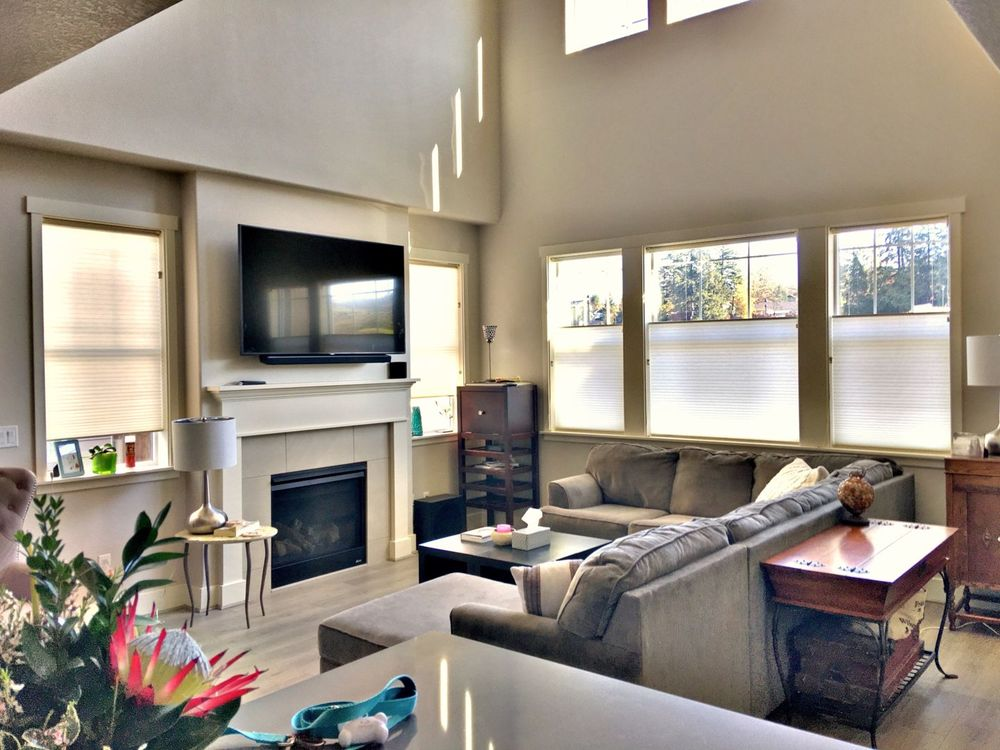 Living space featuring a cozy L-shaped sofa set, a fireplace and a large widescreen TV on the wall. The area features hardwood floors and a tall ceiling.