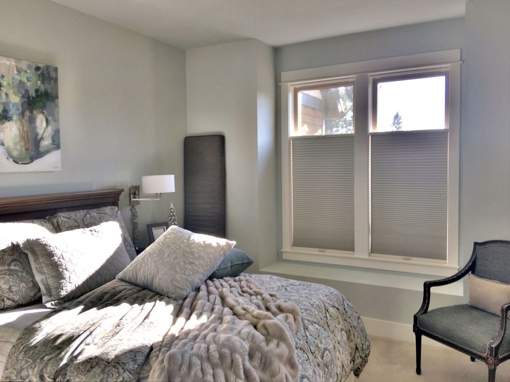 Master bedroom boasting a large luxurious bed with classy table lamps on the side. The room has gray walls and has windows featuring window shades.