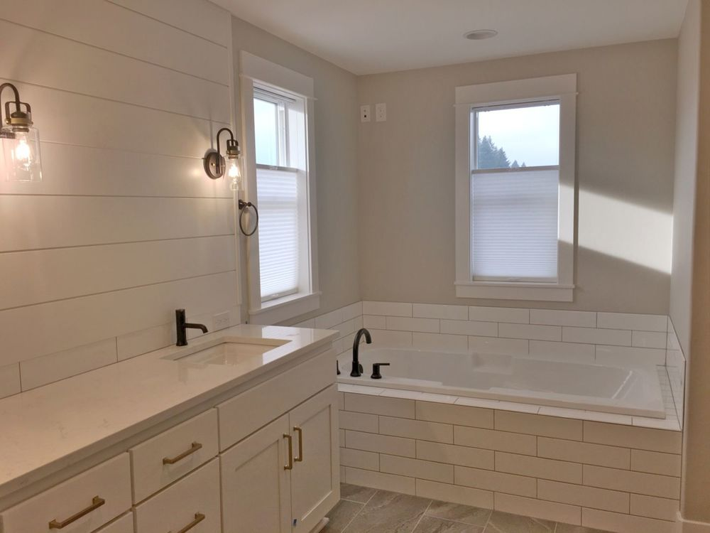 This bathroom offers a sink counter and a drop-in deep soaking tub. The bathroom also features gray tiles flooring and windows with window shades.