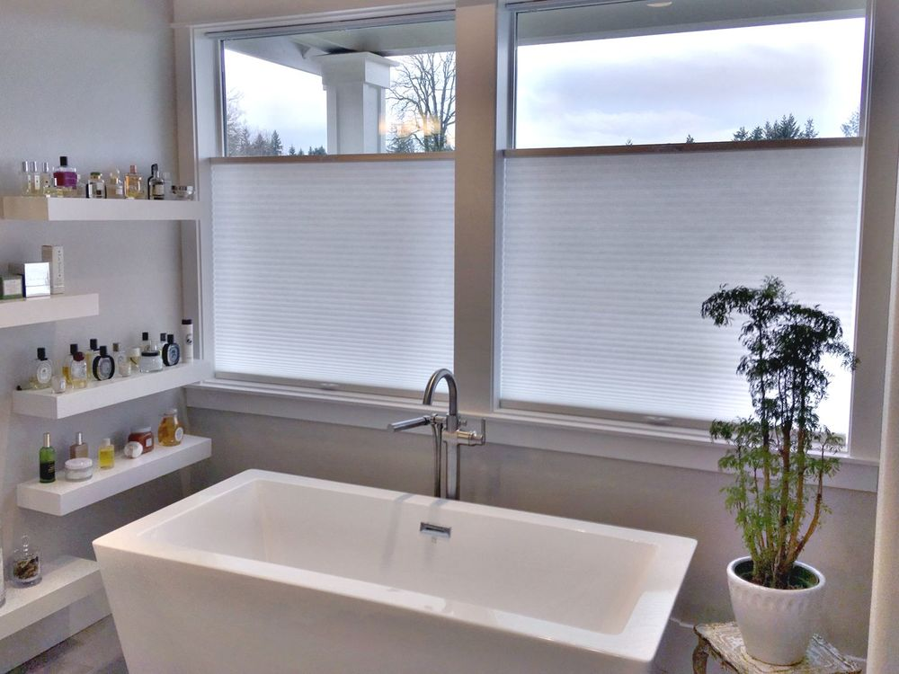 Primary bathroom featuring a freestanding deep soaking tub and built-in shelving on the side, along with glass windows with window shades.