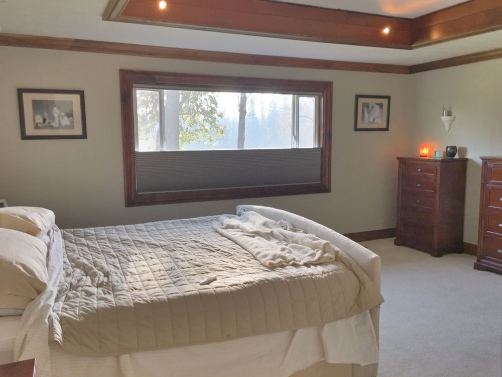 This bedroom offers a cozy bed along with a glass window with a window shade. The room also has carpet flooring and a charming tray ceiling.