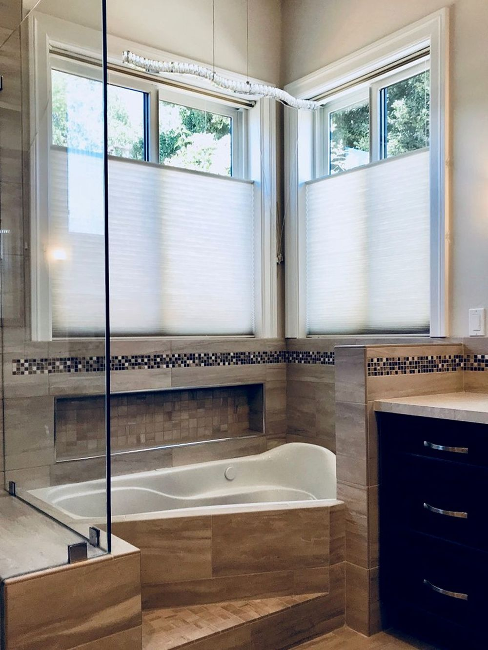 Master bathroom boasting a striking drop-in soaking tub and a walk-in shower room. The room feature windows with window shades as well.