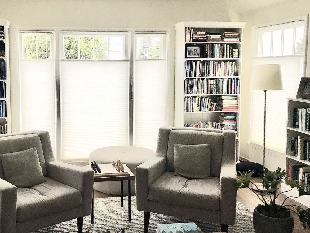 This living space features multiple freestanding bookshelves filled with books. There's a pair of modern gray chairs as well. The windows are covered by window shades.