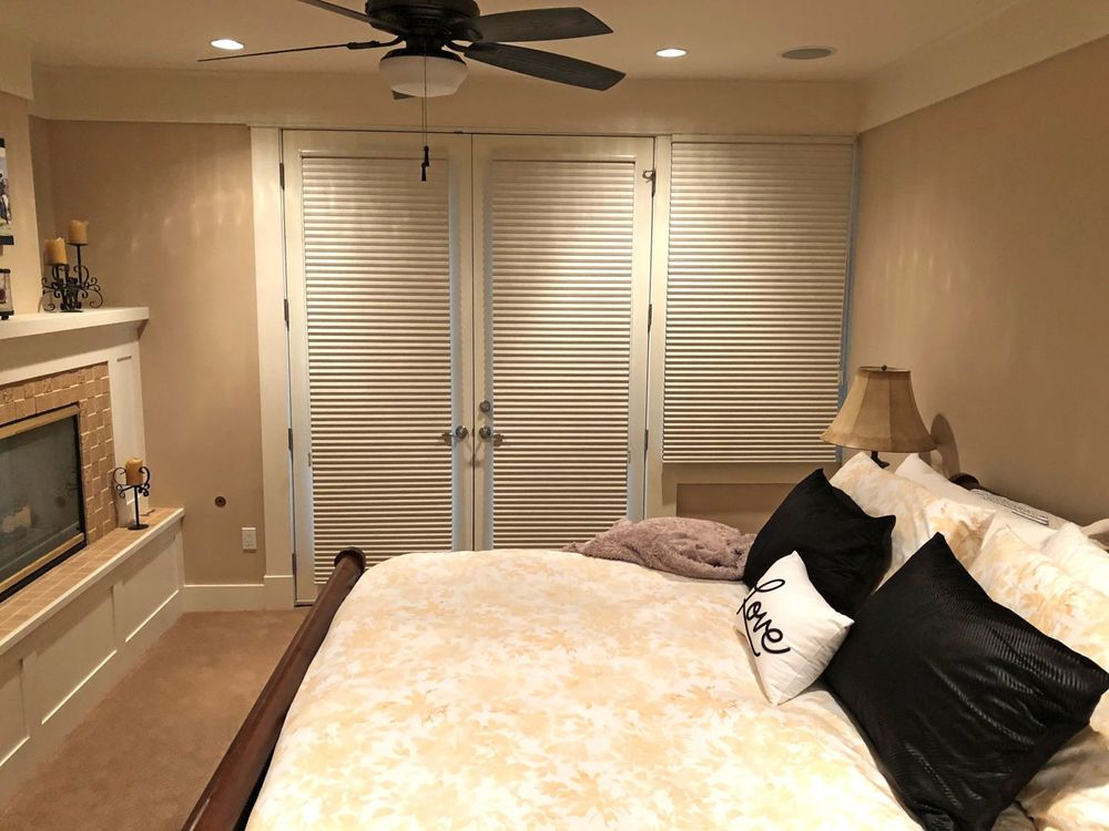 This guest room offers a large and cozy bed set with table lamps on both sides. There's a fireplace as well. The room also features brown walls and carpet flooring.