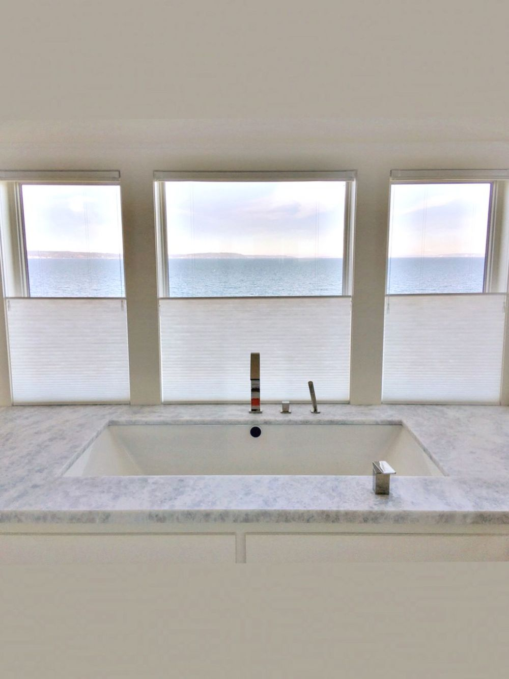 A close up look at this bathroom's drop-in soaking tub by the glass windows, covered by window shades.