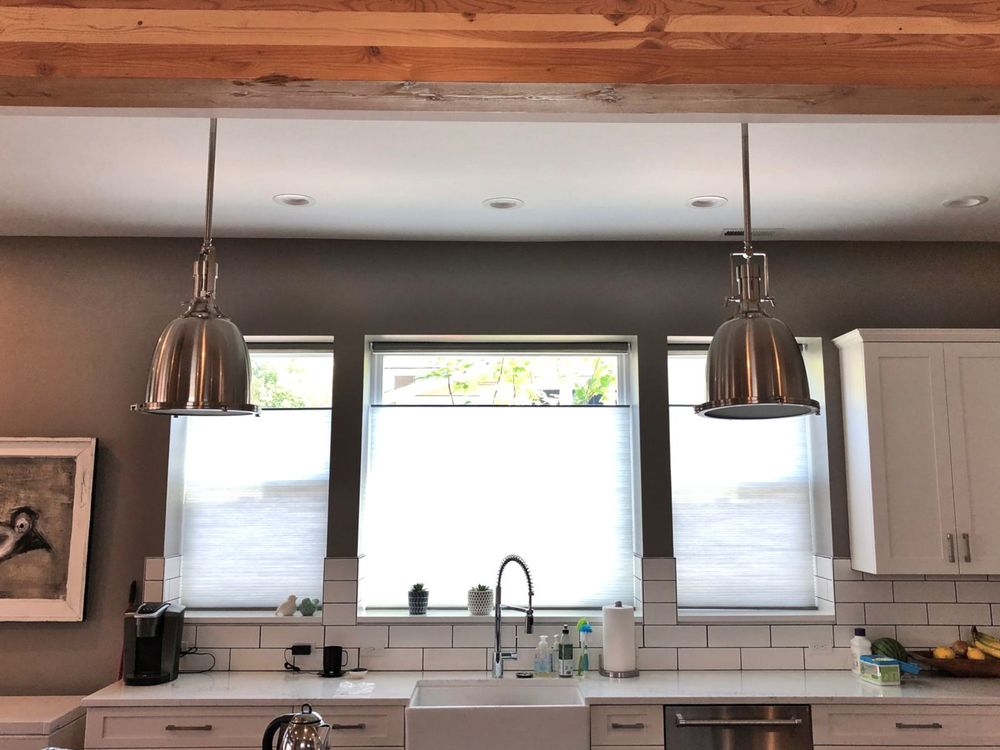 A kitchen with white cabinetry, white tiles backsplash and a white kitchen counter, along with gray walls and a ceiling with exposed beams.