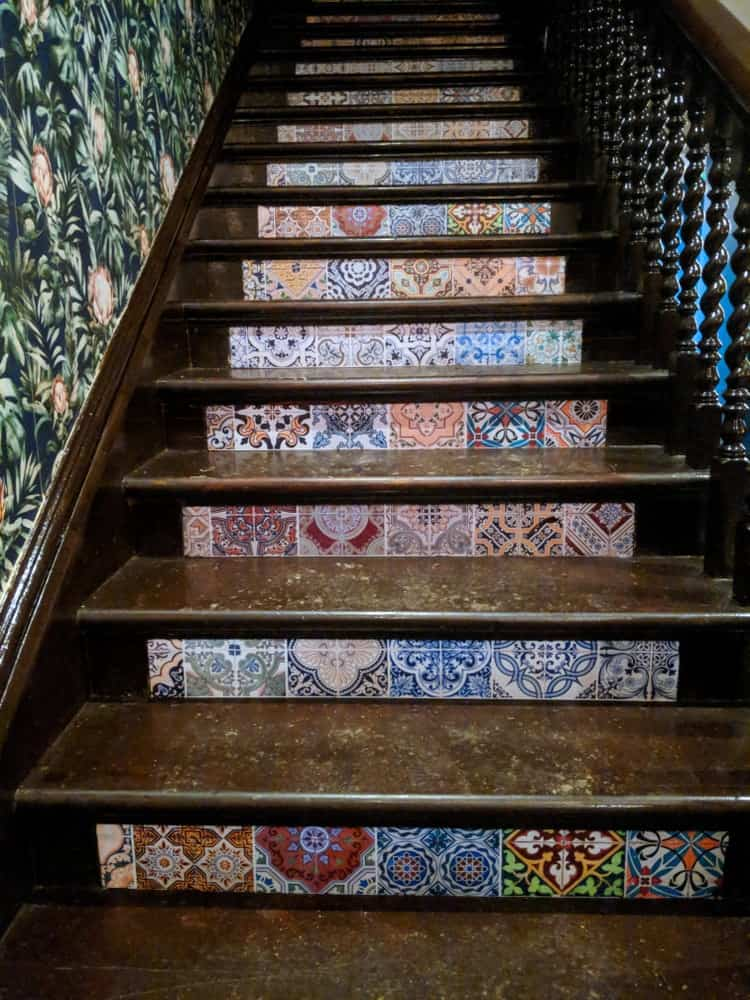 Victorian-patterned ceramic tile stair risers on a distressed staircase.