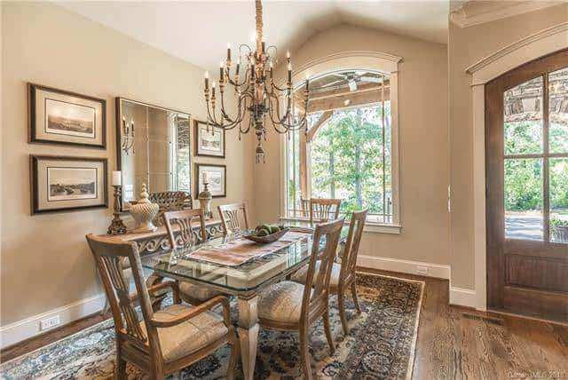 This formal dining area has an elegant glass-top rectangular dining table topped with a majestic decorative chandelier that pairs well with the patterned area rug underneath the dining set.