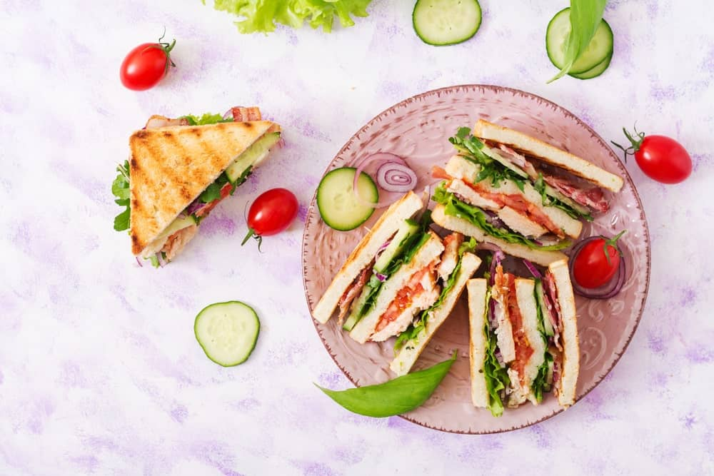 Club sandwich with tomatoes and cucumber slices.