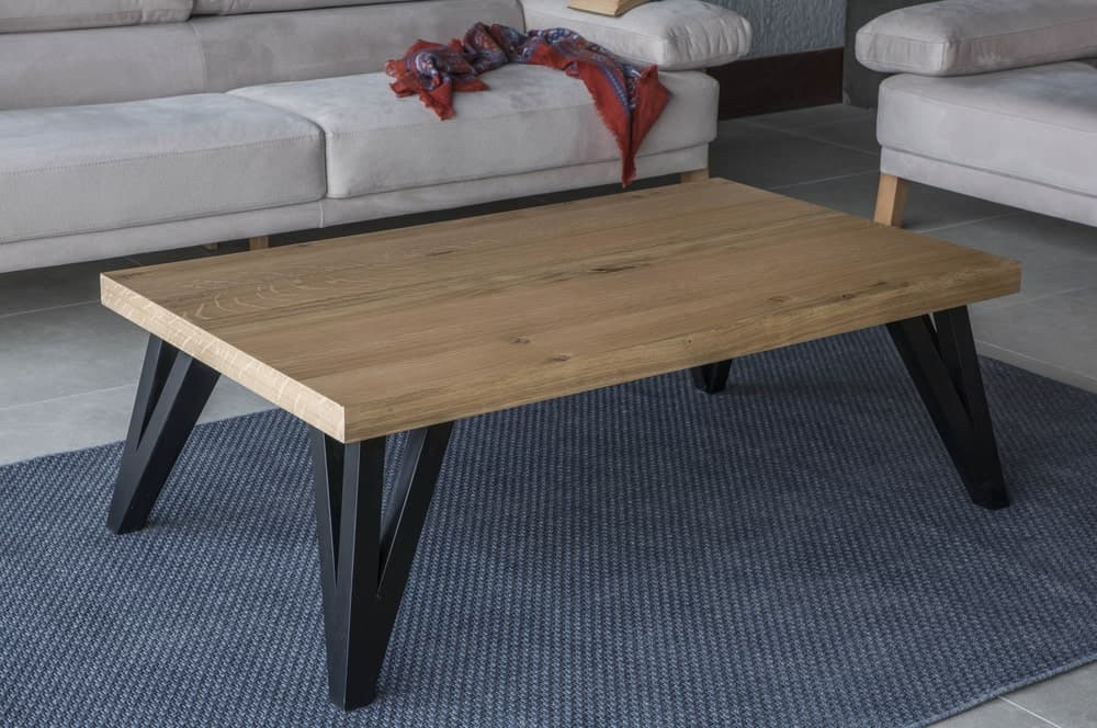 A beautiful wood-top coffee table with black painted legs on a dark gray area rug.