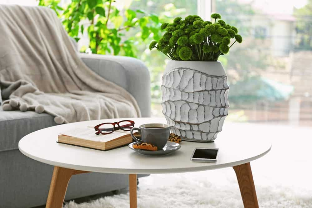 A simple and cozy wooden elliptical coffee table with a white ornamental vase on top.
