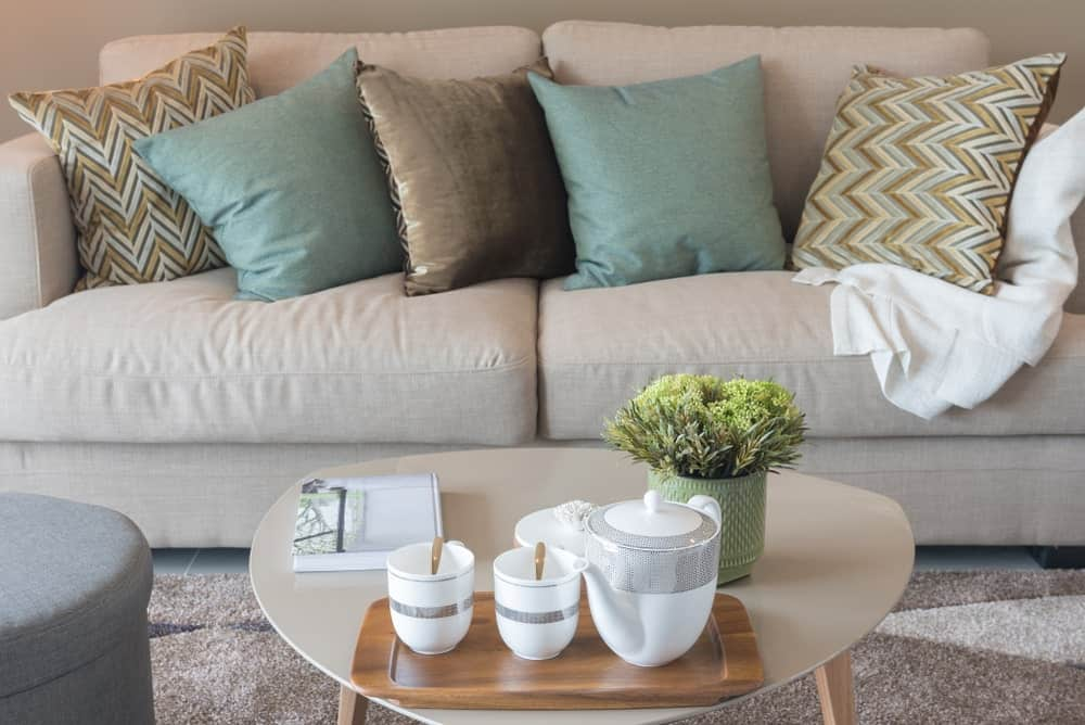 A modern coffee table with an irregular curved shape matching the color of the sofa behind it.