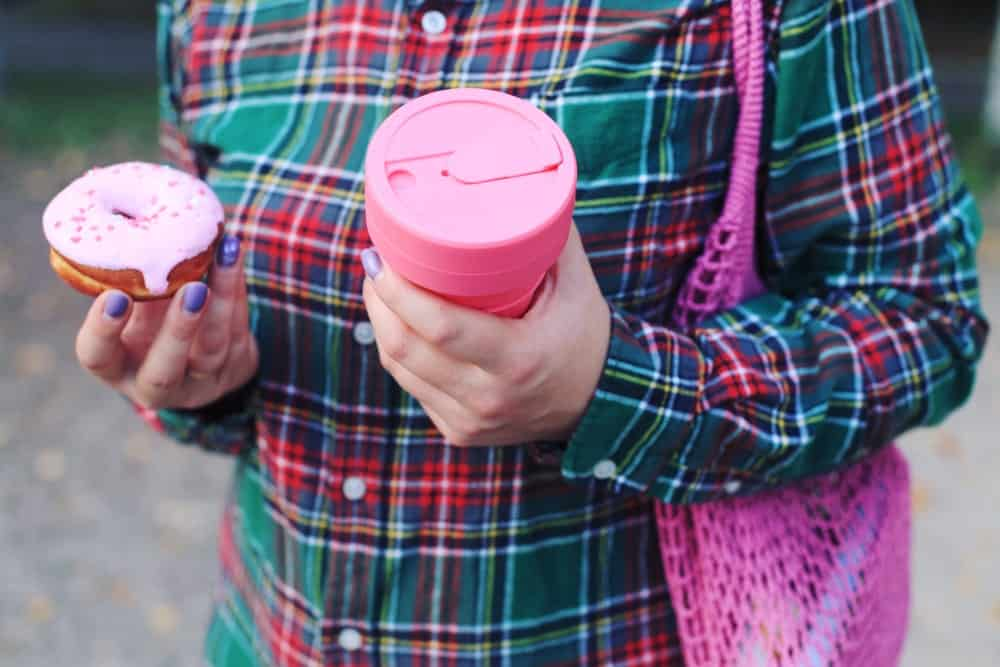 Person holding a collapsible zero waste cup on one hand and a donut on the other.