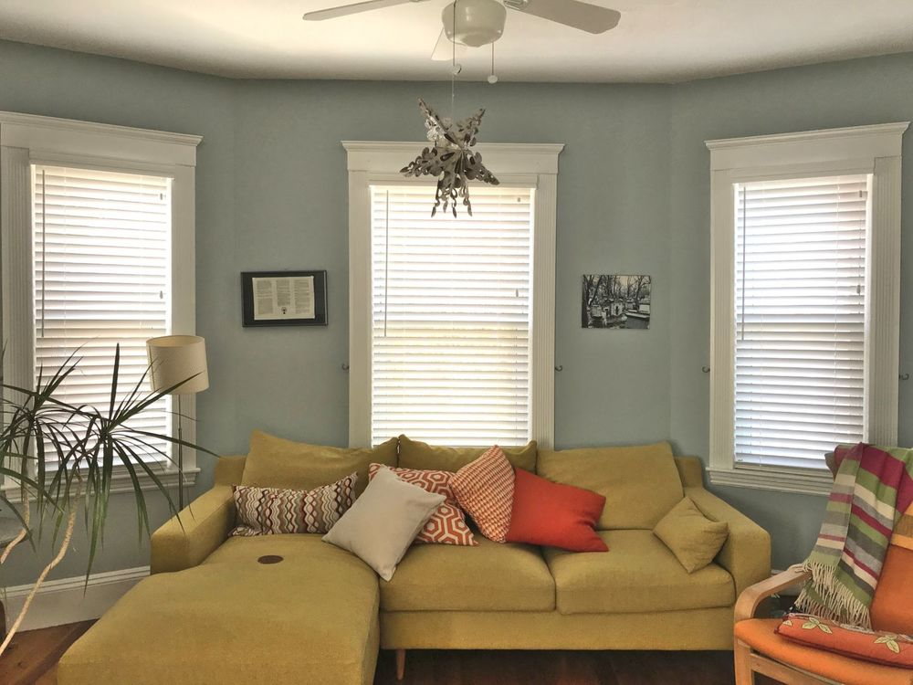 A focused look at this living space's modern brown sofa set surrounded by blueish gray walls and windows with window blinds.