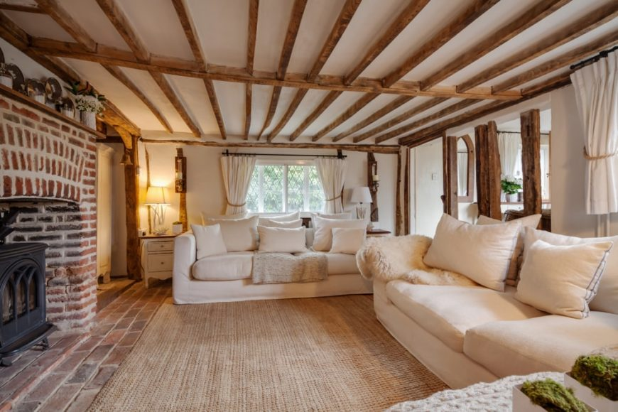 Cottage style living room with beam ceiling and sofa facing the brick fireplace.