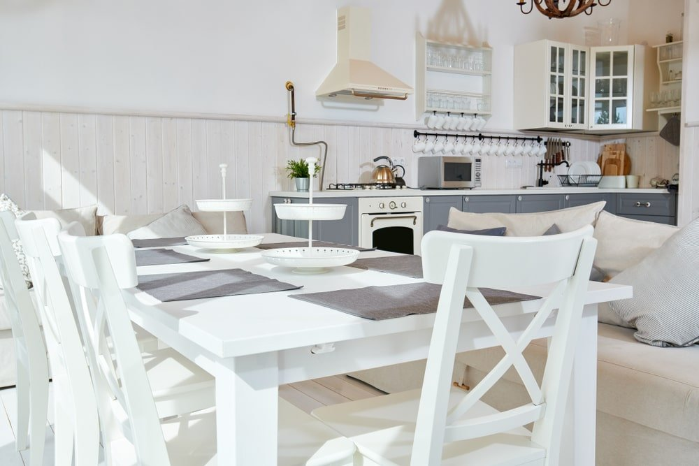 This is a bright and airy Cottage-style dining room right beside the kitchen complemented by it white wooden dining set paired on one side by a creme-colored sofa.