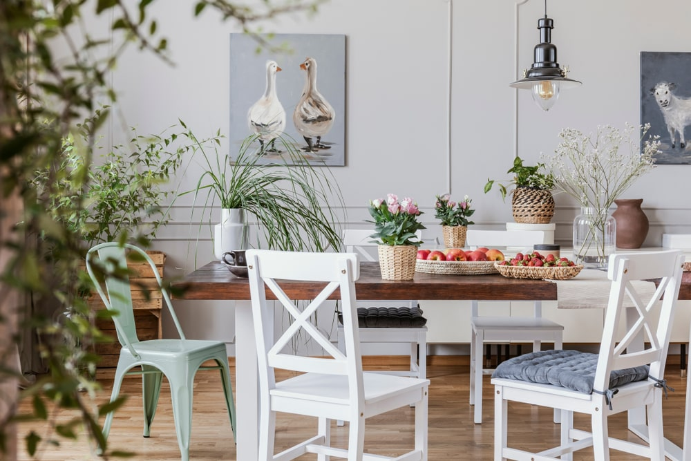 This cozy Cottage-style dining room has beautiful light hardwood flooring that goes well with the wooden dining table with white wooden legs. This is matched by the wooden cross-backed dining chairs with strap-on cushions.