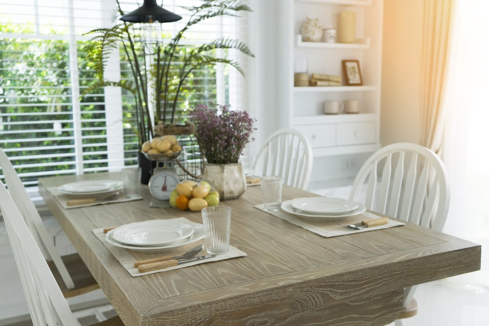 This is an intimate Cottage-style dining room that can sit four people on its wooden slat-backed chairs that pairs well with the wooden dining table. These are brightened by the window at the head of the table with blinds.