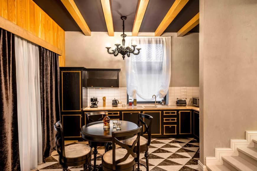 This informal dining area is right inside the kitchen that shares the same theme of black and beige palette. It has a small round black table paired with black cross-backed chairs with beige cushions. These matches well with the tiled flooring that has black and beige hues.