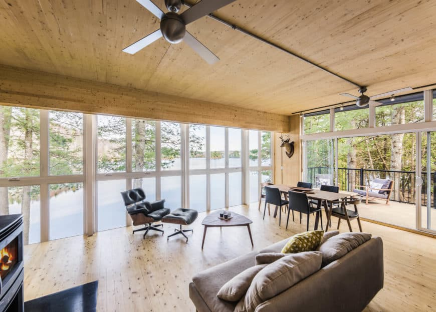 This Cottage-style dining area is part of a large room that also houses the kitchen and living room area in its wooden ceiling, matching hardwood flooring and the glass walls that show a scenic view of the lake. The dining area has a wooden dining table paired with contrasting black chairs.