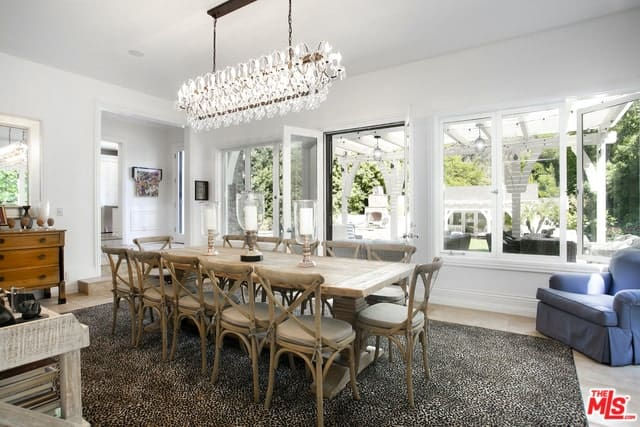 The main feature of this Cottage-style dining room is the large unique decorative chandelier that is hanging over the long wooden dining table. This matches with the surrounding cross-backed chairs over the dark area rug of the light hardwood flooring.