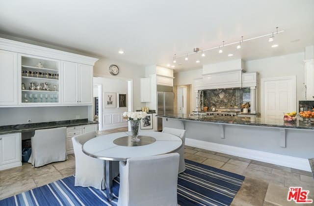 This is an informal Cottage-style dining area right beside the kitchen. It has a round modern dining table surrounded by dining chairs covered in light gray slip covers that go well with the blue-striped area rug underneath.