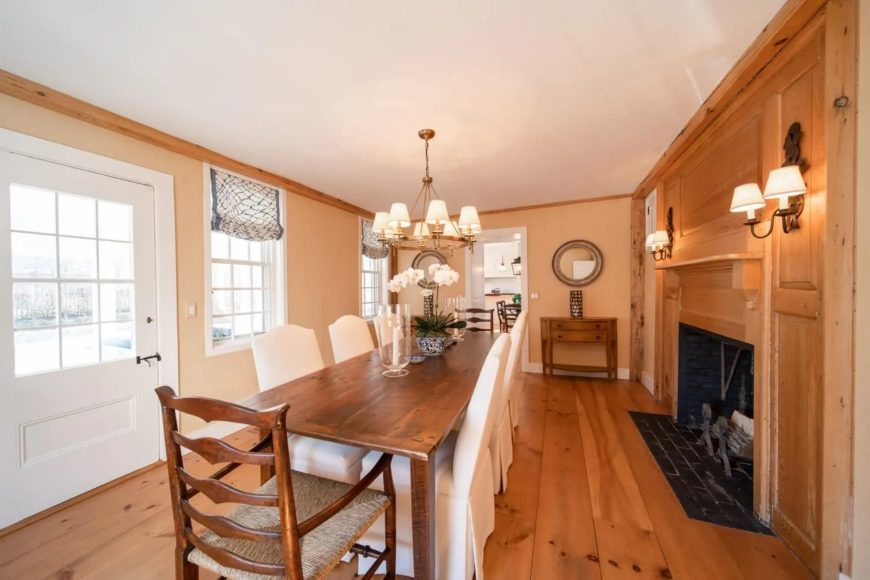 The charming long wooden dining table of this Cottage-style dining room is a perfect match for the hardwood flooring that blends well with the wooden mantle of the fireplace. This is flanked by wall-mounted lamps that match the chandelier.