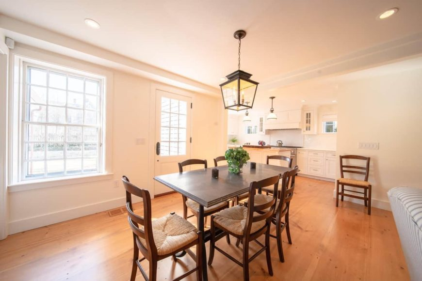 This is a simple Cottage-style dining room with a hardwood flooring that complements the dark wooden dining chairs that has woven wicker seats. These chairs are perfectly matched for the small wooden dining table topped with a lantern-like pendant light.