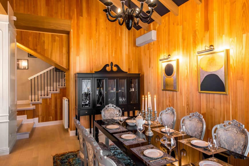 This Cottage-style dining room has an elegant dining set of slick black table and light gray chic chairs with floral cushions. These are well paired with the colorful patterned area rug that adds a dash of color to the light hardwood flooring.
