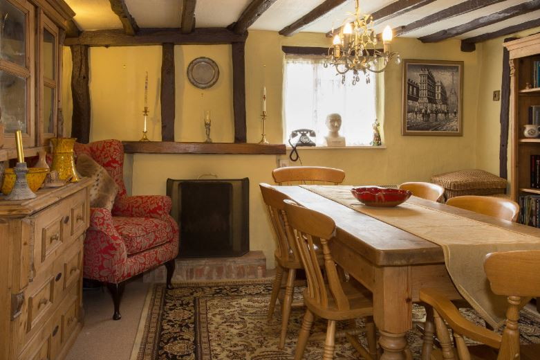The elegant golden chandelier of this Cottage-style dining room is a nice contrast to the rustic ceiling with its dark wooden beams. This is a nice background for the homey wooden dining set over the patterned area rug.