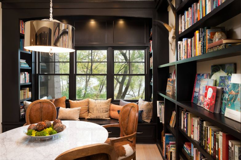 There is a unique charm to this Cottage-style dining room with its built-in bookshelves and reading nook with the same dark wooden finish. This makes the white round dining table stand out surrounded by wooden oval-back dining chairs.