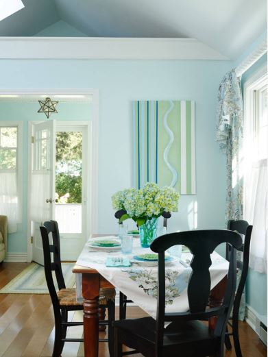 The bright pastel blue tone of the walls of this Cottage-style dining room is a nice contrast for the black wooden dining chairs surrounding the wooden dining table that is topped with a charming table cloth.