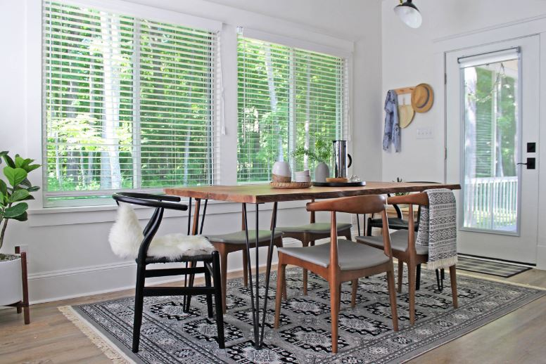 There is beauty in the simplicity of this Cottage-style dining room that has a patterned area rug underneath of the wood-topped dining table with metal legs. This is surrounded by wooden chairs and black wishbone chairs on each head.