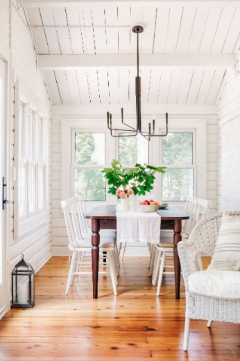 The white dining chairs of this Cottage-style dining room blends well with the white wooden doors with a charming finish that matches with the wooden cathedral shiplap ceiling. This is then contrasted by the hardwood flooring and the simple iron chandelier.
