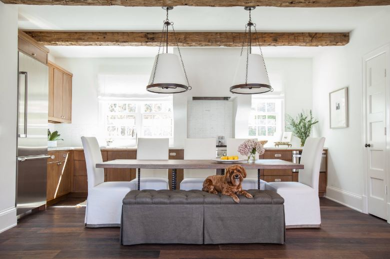 The dark hardwood flooring of this Cottage-style dining room and kitchen is a nice contrast to the white upholstery of the dining chairs, white walls and white ceiling along with its white pendant lights hanging over the wooden table.
