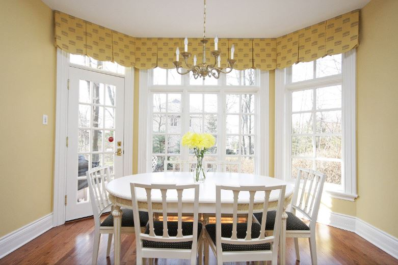 This is a lovely Cottage-style dining room with a sunny demeanor to its yellow walls and the yellow shades of the white French windows and door. These bring in an abundance of natural lighting for the white wooden dining set.