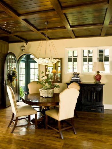 The dark brown wooden coffered ceiling is a nice match for the dark wooden round dining table and the hardwood flooring. These are then complemented by the beige walls, upholstered chairs and the decorative bowl pendant light.