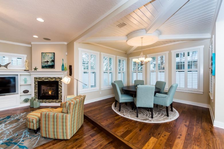 This is a dining area with an open wall right beside the living room and its fireplace. The dining area has a white wooden shiplap ceiling hanging a small chandelier over the dark wooden dining table surrounded by light gray cushioned dining chairs.