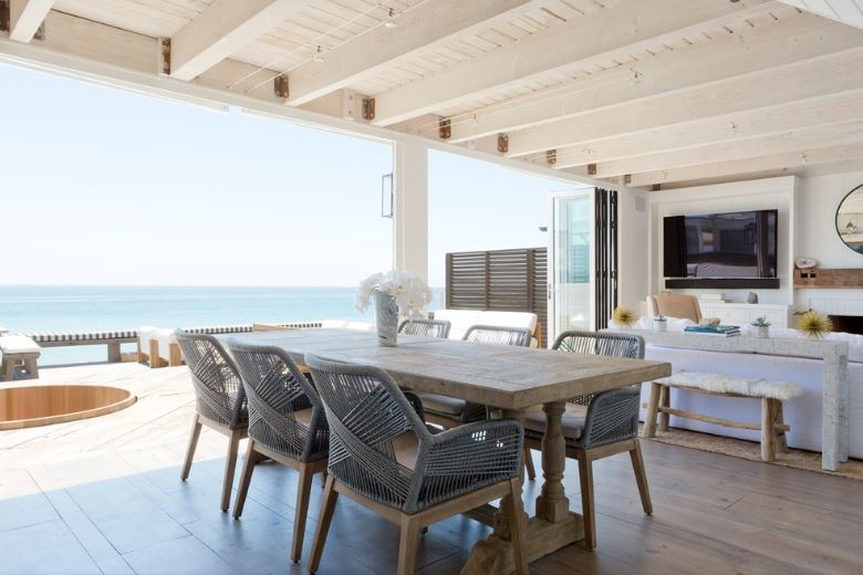 This Cottage-style dining room has a great view of the sea with its open wall on one side. It goes well with its white wooden ceiling with exposed beams and the wooden dining table that matches well with the hardwood flooring and its wooden chairs that has light gray woven wicker finish.