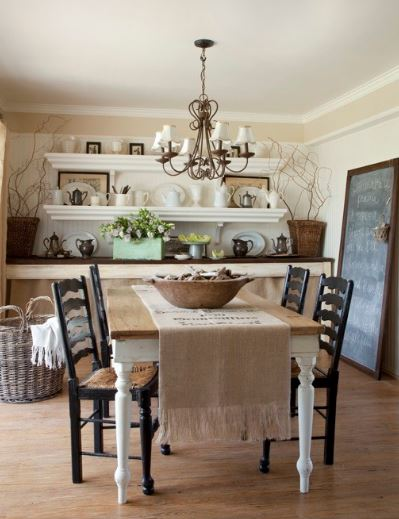 The charming wooden dining table of this Cottage-style dining room is topped with a detailed decorative thin chandelier. The wooden table is surrounded by dark wooden dining chairs with woven wicker seats.