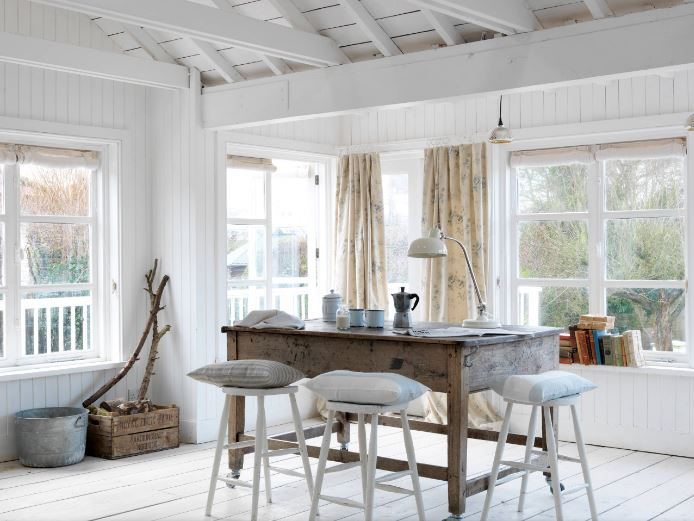 This bright and charming Cottage-style dining room has an arched ceiling with exposed wooden beams and a shiplap white finish that pairs well with the wooden flooring and the walls filled with windows that bring in natural lighting to the wooden dining set.