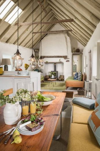 This Cottage-style dining area is part of a great room that also houses the living room under its cathedral ceiling with exposed wooden beams. The wooden dining table has metal legs and is paired with a built-in bench with cushions.
